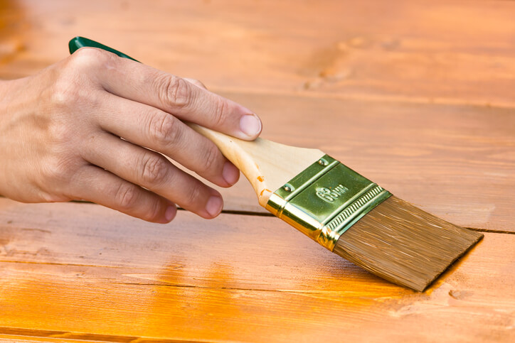 hand painting wood boards with brush, closeup