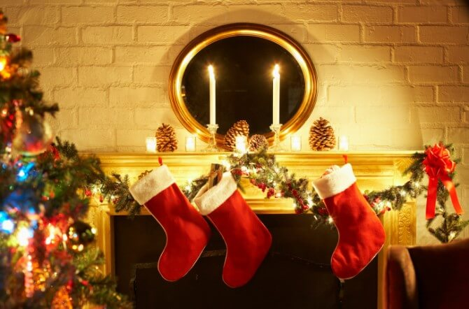 Fireplace mantle decorated with stockings and candles