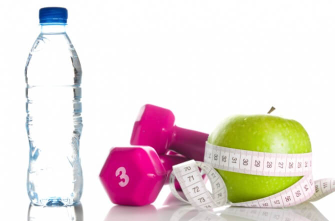 dumbbells with measuring tape around apple and bottle