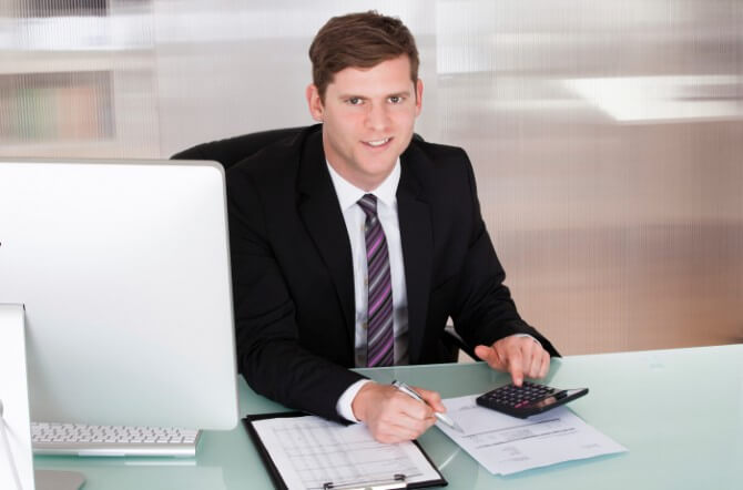 Happy young man calculating finances