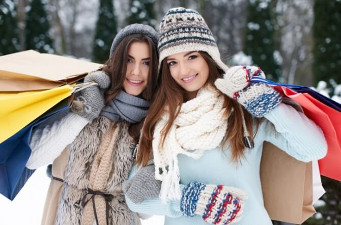Two women with shopping bags in the snow