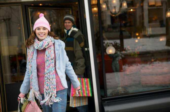 Woman in Winter Clothing Walks Out of a Shop Carrying Shopping Bags, Her Boyfriend in the Background