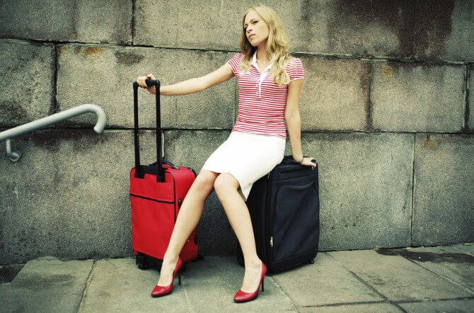 woman sitting on her luggage and waiting