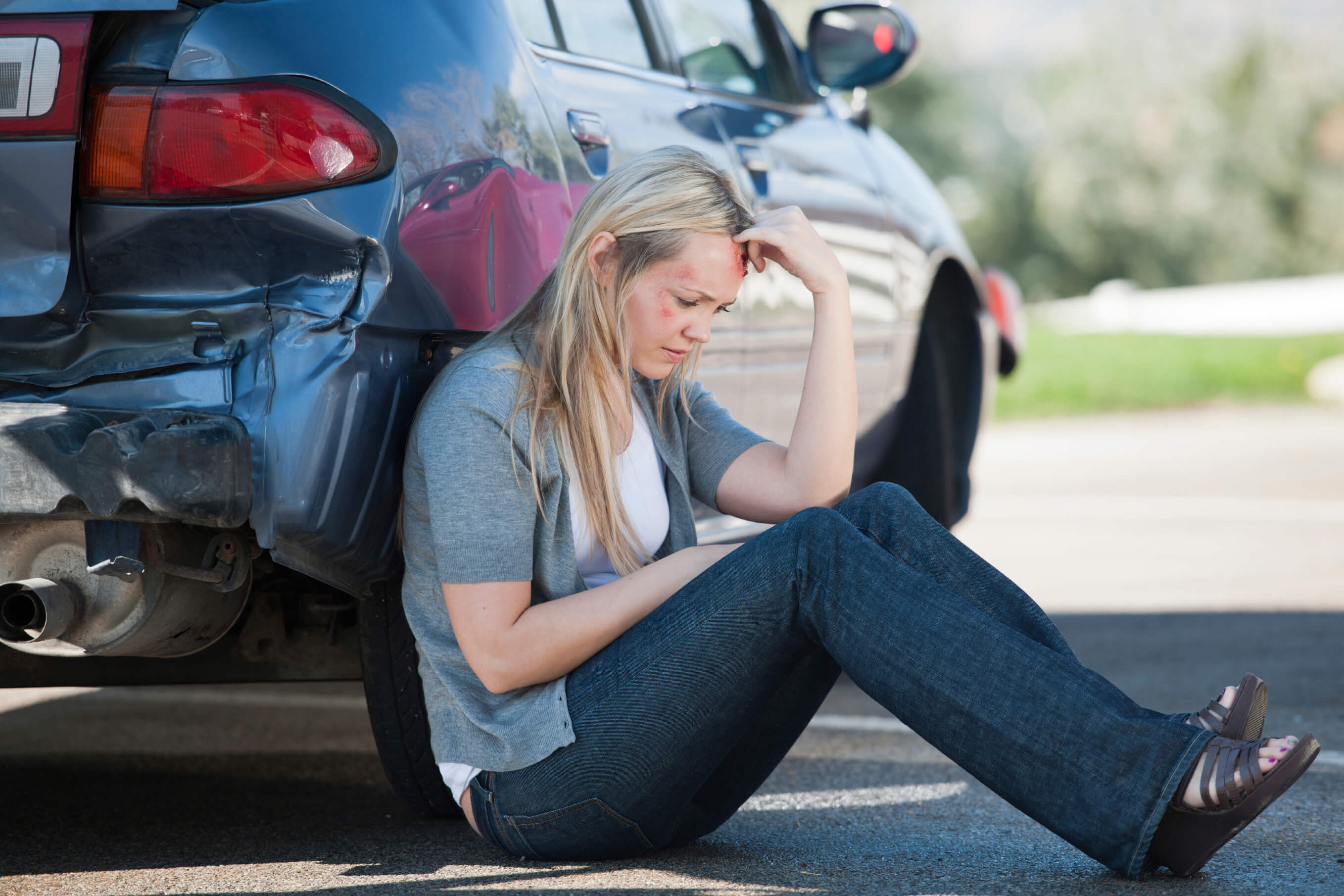 Woman sitting by car after accident