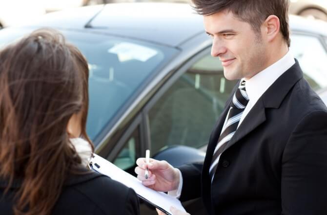 Car dealer writing down a woman's information