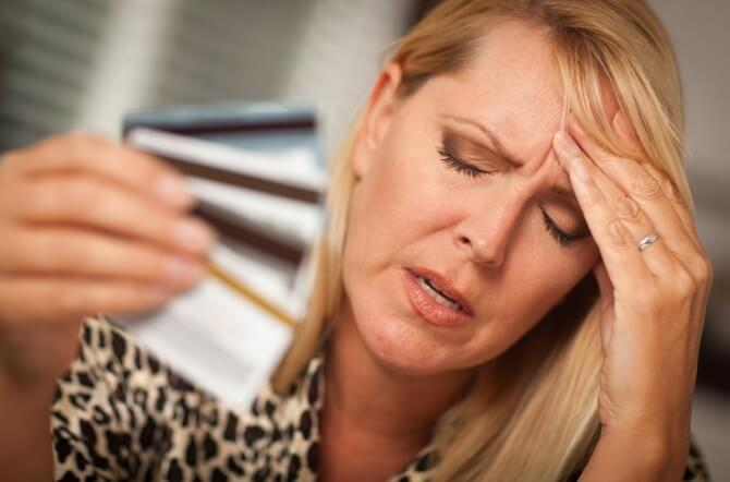 Woman holding credit cards and stressed