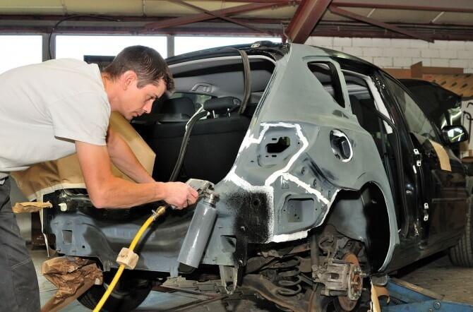 Man working at a body shop on a damaged car