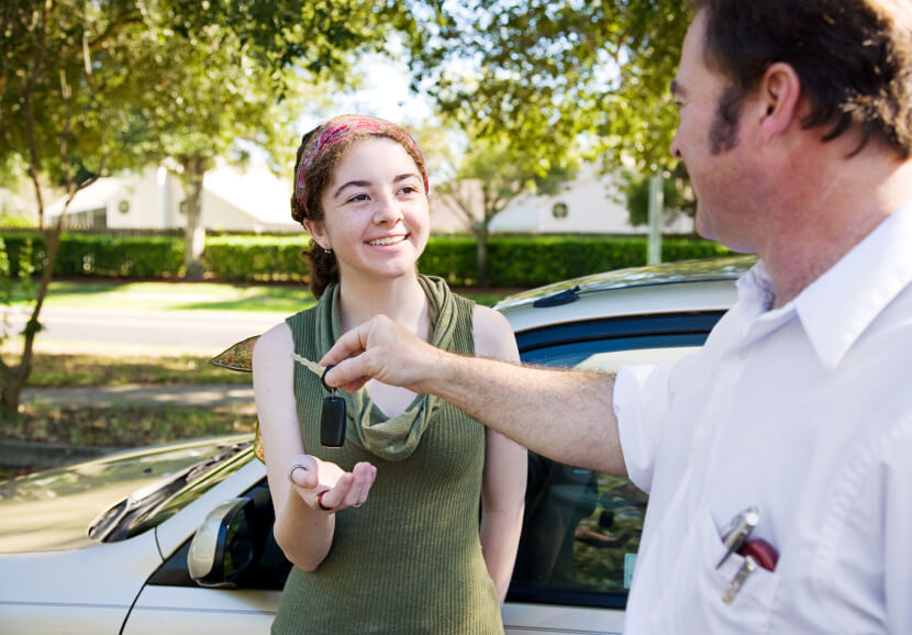 Young woman being handed the car keys by her father or driving instructor.