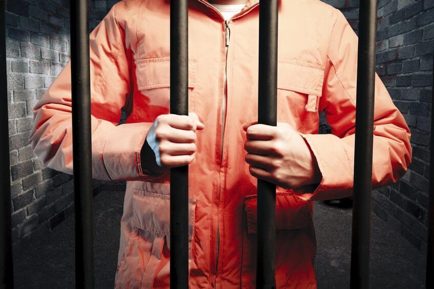 Man in orange jumpsuit in jail