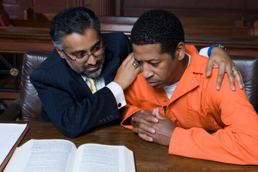 Lawyer embracing criminal in court