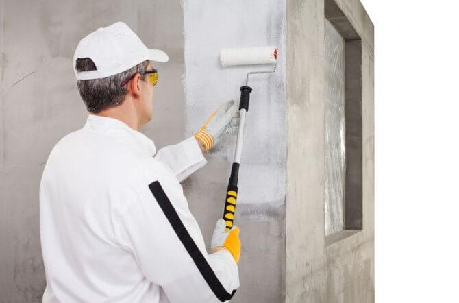 man in white baseball cap holding paint roller