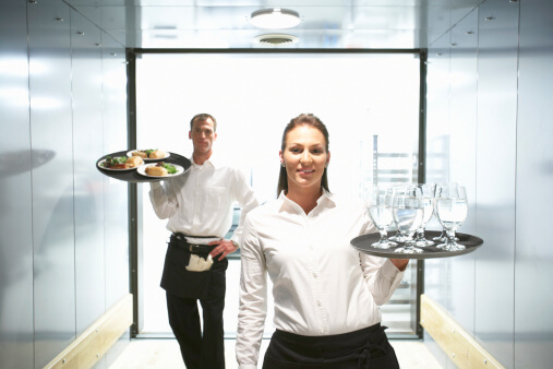 Waiter and waitress holding food and drink on trays, portrait