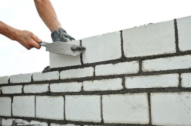 man stacking bricks