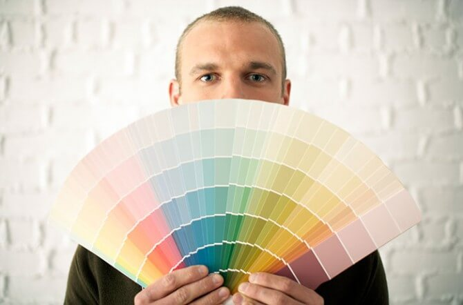 man holding paint color swatches