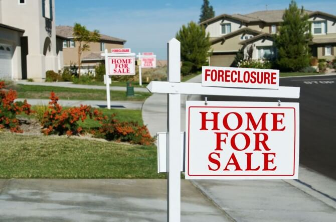 Row of homes with foreclosure signs