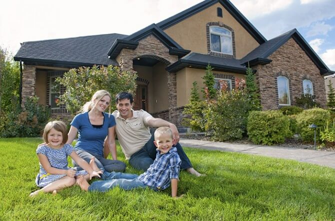 family sitting on grass in front of house