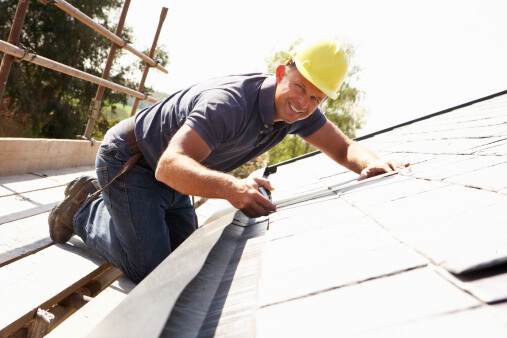 Roofer Working On Exterior Of New Home
