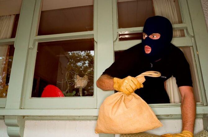 burglar leaning out of house window