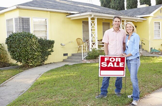 "couple in front of ""for sale"" sign and house"