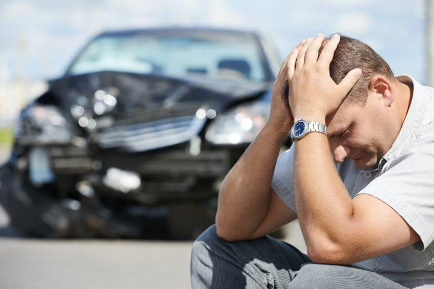 Man sitting in front of car that has been involved in collision