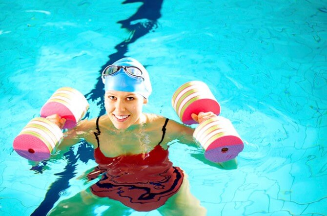 woman lifting weights in swimming pool