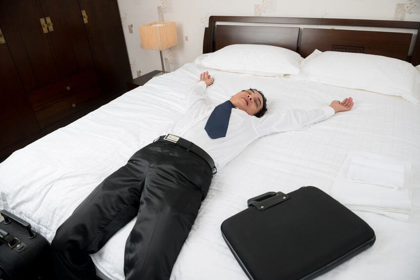 man laying on white sheets on king size bed