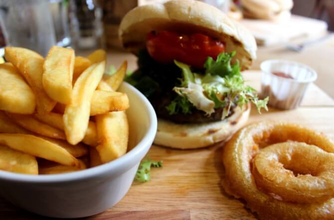 Image of gourmet burger, chunky chips, onion rings and salad