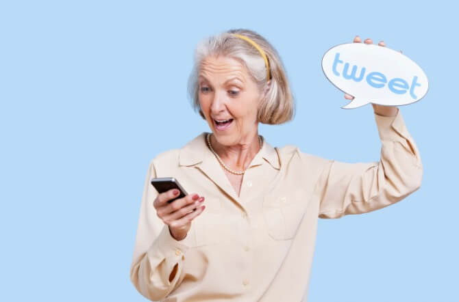 Senior woman in casuals using social media on her Smartphone against blue background