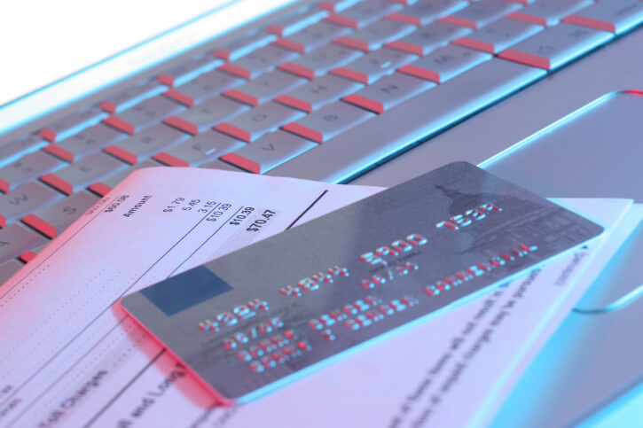 Close-up of a credit card with a bill on a laptop