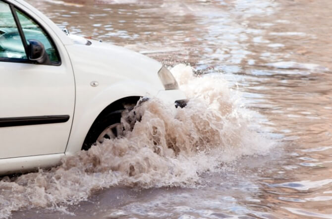 Car drives through flooded road
