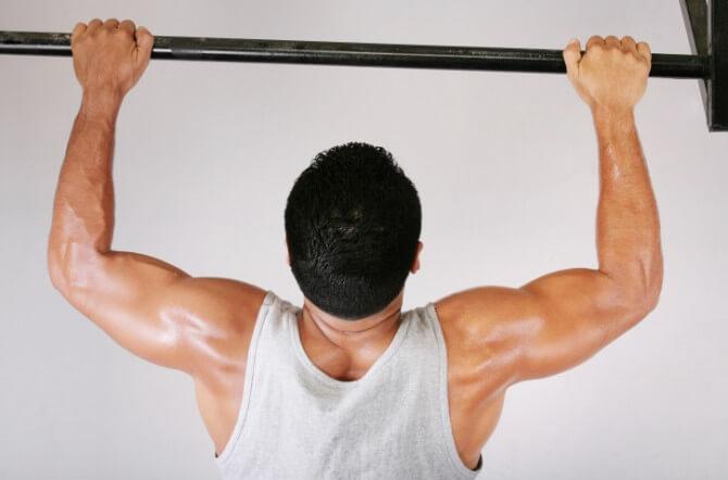 Reaching Goal: Strong man doing pull-ups on a bar