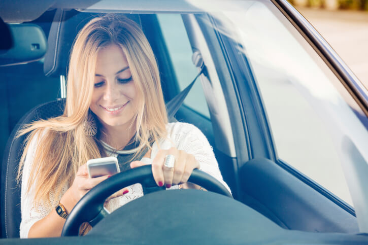 Young Woman Sending Messages while Driving