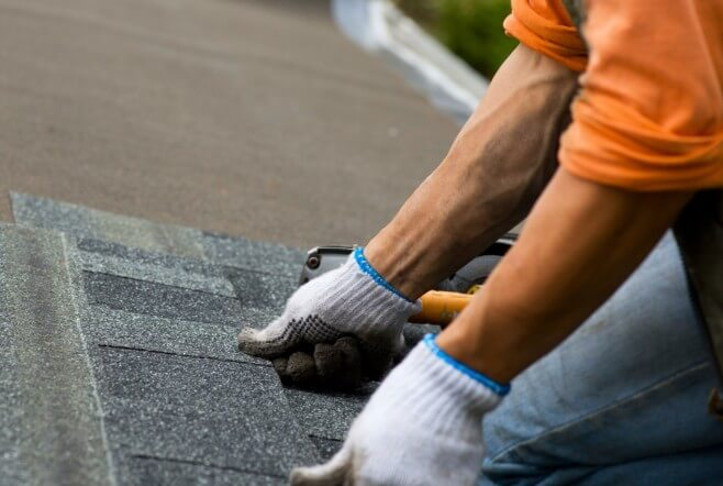 pressing down shingles white gloves orange shirt