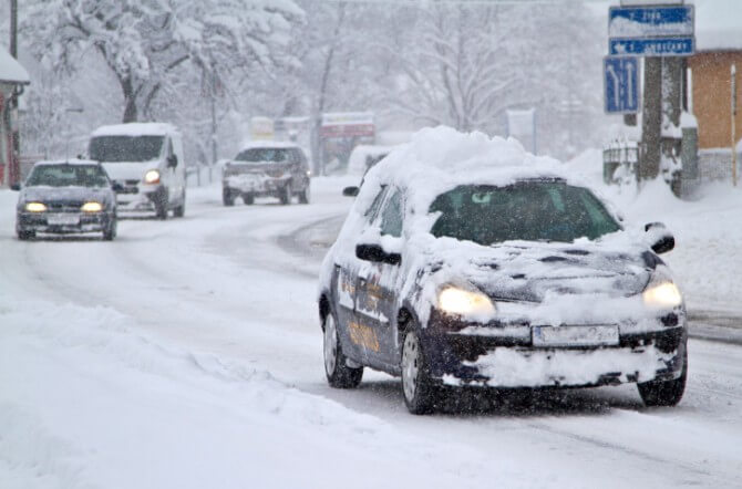 small car driving in snow