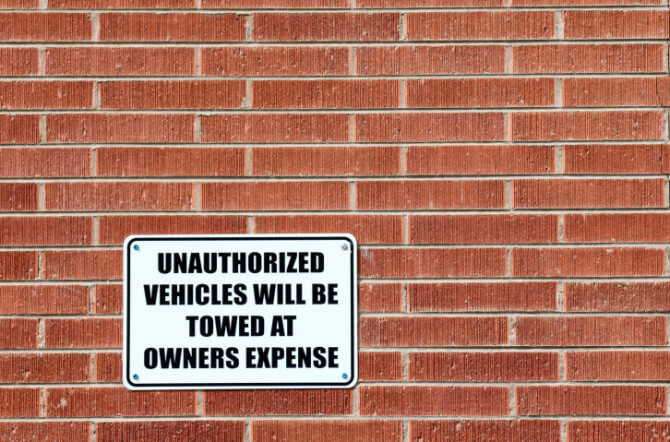Predatory Towing- What You Need to Know and How to Protect Yourself - Parking Sign